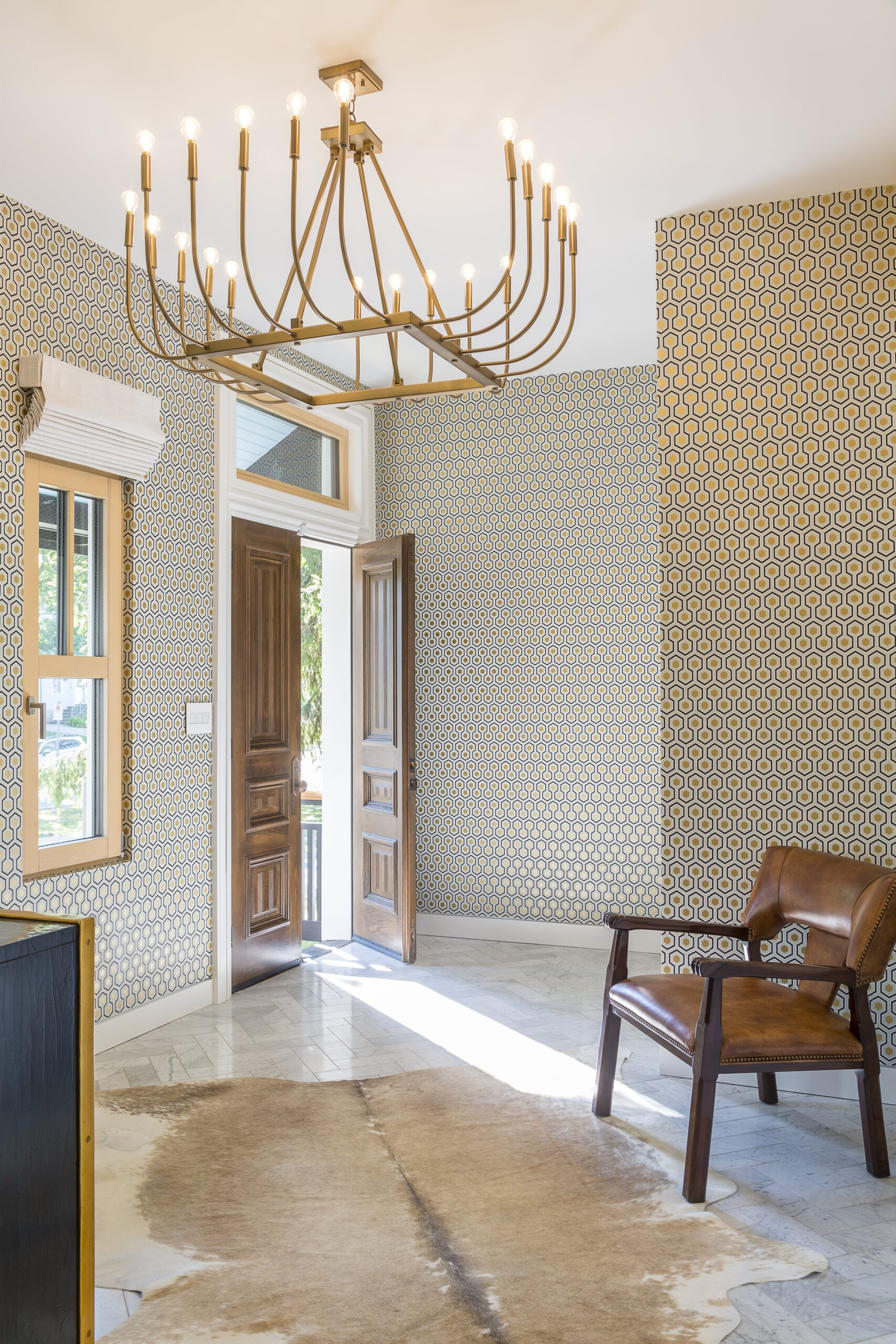 historic renovation entryway with modern gold chandelier and geometric printed wallpaper