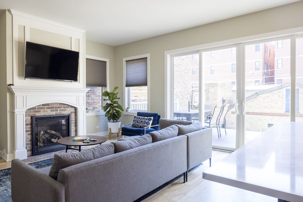 living room with all glass sliding patio doors and traditional brick fireplace